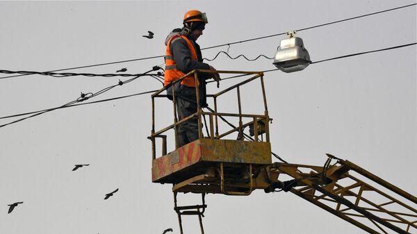 Работник коммунальной службы ремонтирует фонарь