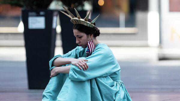 Девушка в костюме Статуи Свободы на Таймс-сквер в Нью-Йорке