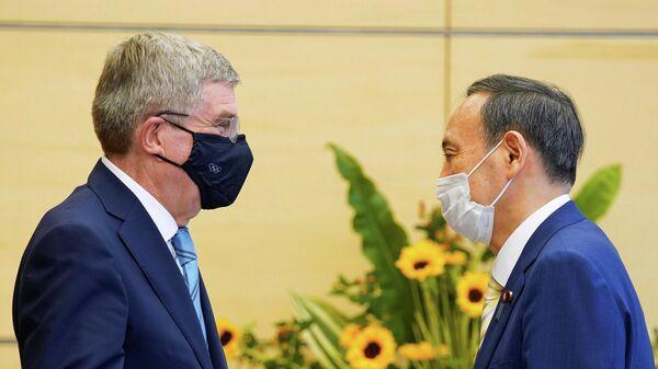 Президент Международного олимпийского комитета (МОК) Томас Бах (слева) и премьер-министр Японии Есихидэ Суга