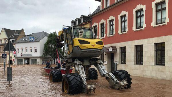 Автомобиль специального назначения везёт лодку в затопленном районе Эранг в Трире, западная Германия
