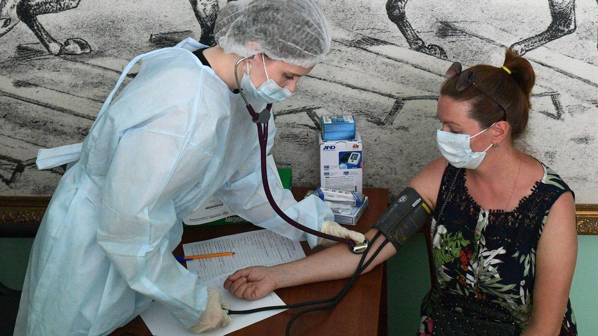 Медицинский сотрудник измеряет давление женщине перед вакцинацией от COVID-19 в Санкт-Петербурге - РИА Новости, 1920, 23.07.2021
