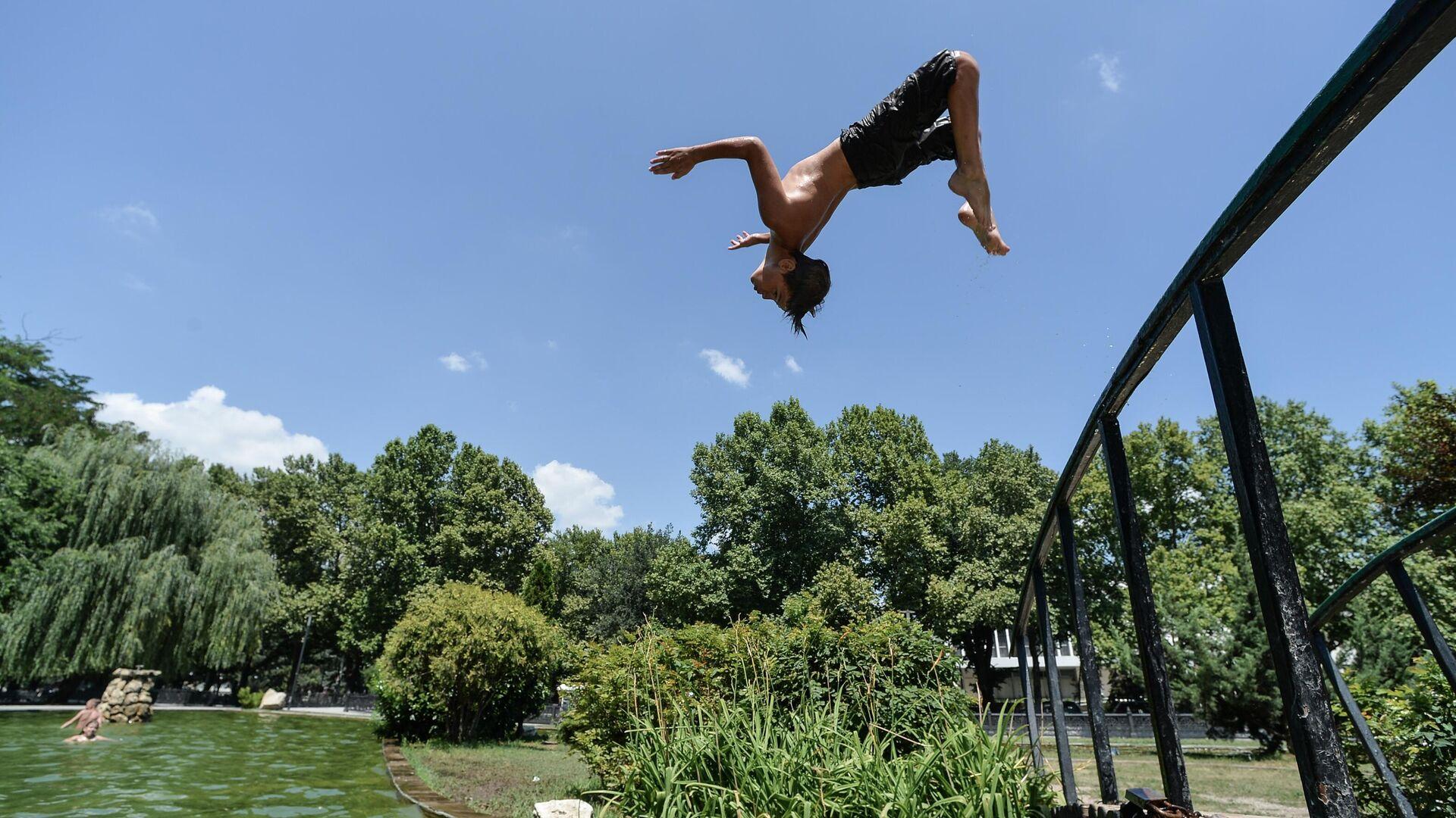 Мальчик прыгает в воду в жаркий день в Центральном парке культуры и отдыха Симферополя - РИА Новости, 1920, 03.08.2021