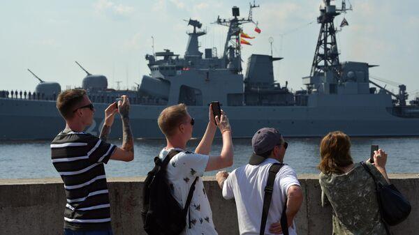 Люди на набережной наблюдают за подготовкой кораблей ВМФ РФ к параду, посвященному Дню Военно-морского флота РФ, в Кронштадте