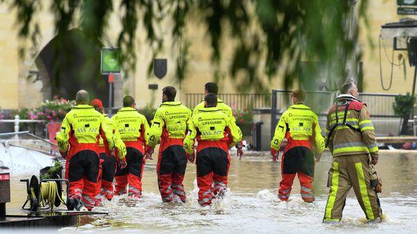 Спасатели идут по затопленной улице после проливных дождей в Валкенбурге, Нидерланды