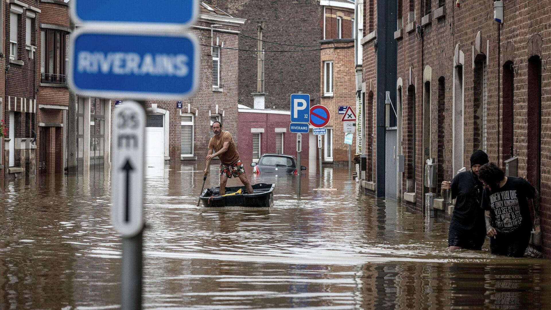 Мужчина плывет на лодке по жилой улице после наводнения в Англере, Бельгия - РИА Новости, 1920, 27.07.2021