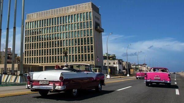 Ретро-автомобили с туристами около посольства США в Гаване, Куба