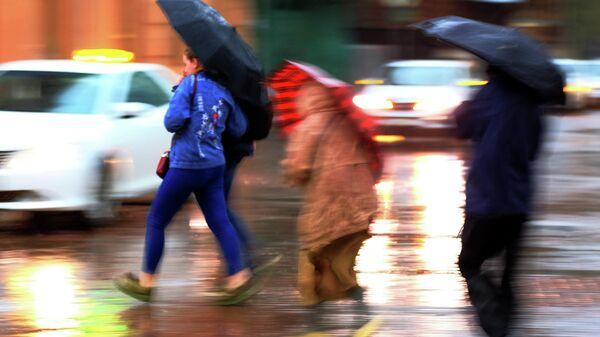 Пешеходы на улице во время сильного дождя