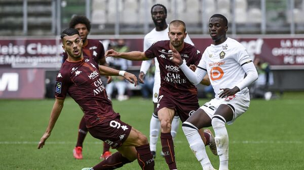 (From L) Metz's French forward Georges Mikautadze and Metz's Senegalese forward Ibrahima Niane fight for the ball with Lille's US forward Timothy Weah during the French L1 football match between FC Metz and Lille OSC at Stade Saint-Symphorien in Longeville-les-Metz, northern France, on August 8, 2021. (Photo by JEAN-CHRISTOPHE VERHAEGEN / AFP)