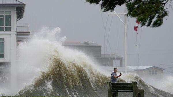 Мужчина фотографирует высокие волны на берегу озера Пончартрейн во время приближения урагана Ида