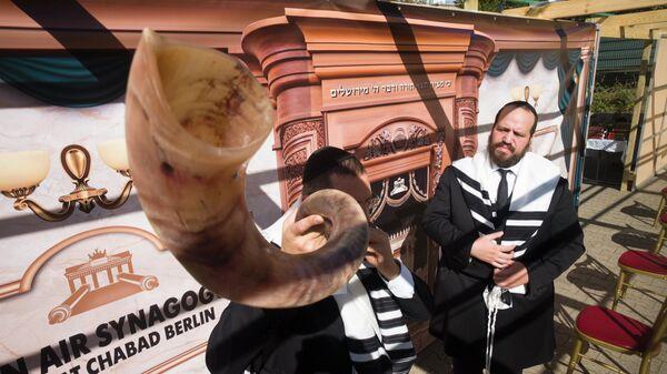 Раввин использует шофар, символ еврейского Нового года Рош ха-Шана в Берлине, Германия