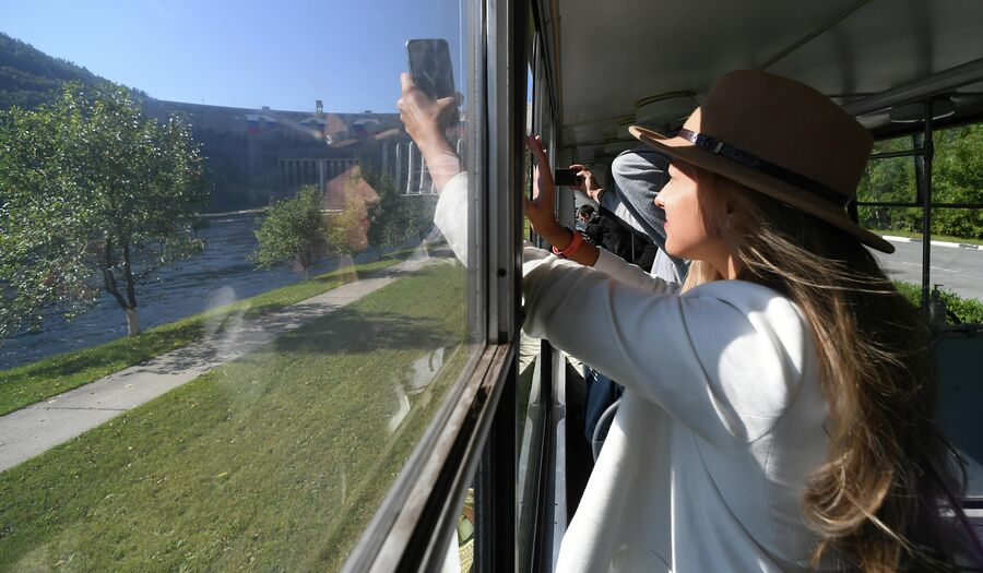 Девушка фотографирует из трамвая плотину Саяно-Шушенской ГЭС на реке Енисей