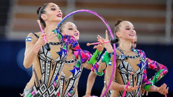 Спортсменки сборной Израиля выполняют упражнения с тремя обручами и двумя парами булав в финале соревнований групп по художественной гимнастике на XXXII летних Олимпийских играх в Токио.