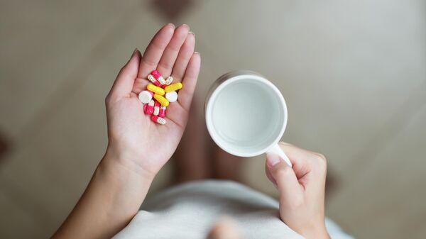 Девушка с таблетками и кружкой воды