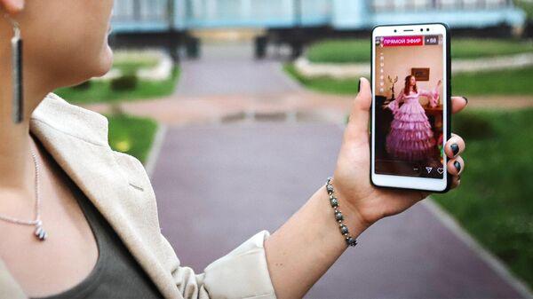 Девушка смотрит онлайн-трансляцию в Instagram