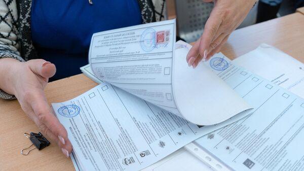 Сотрудник участковой избирательной комиссии во время работы на выборах