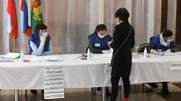 Избирательница получает бюллетень для голосования на избирательном участке в районном Центре культуры и досуга села Аскиз в Республике Хакасия
