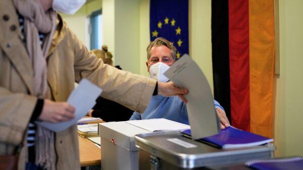 Женщина голосует на одном из избирательных участков в Берлине во время парламентских выборов в Германии
