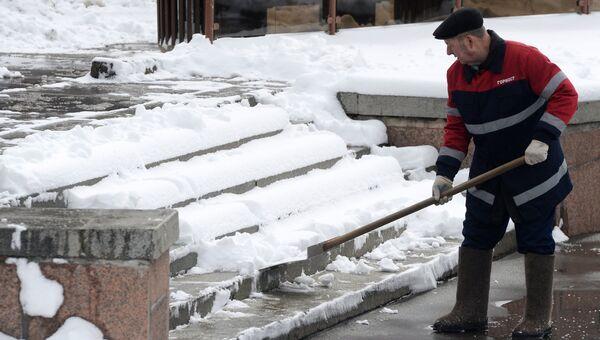 Сотрудник коммунальных служб убирает снег на улице