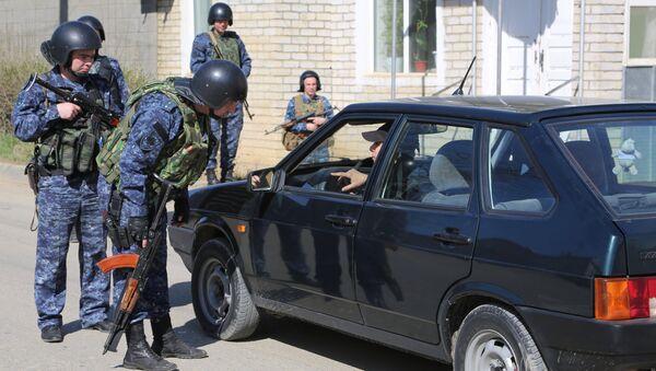 Сотрудники полиции досматривают автомобиль на месте проведения контртеррористической операции у частного дома в Буйнакске. Фото с места события