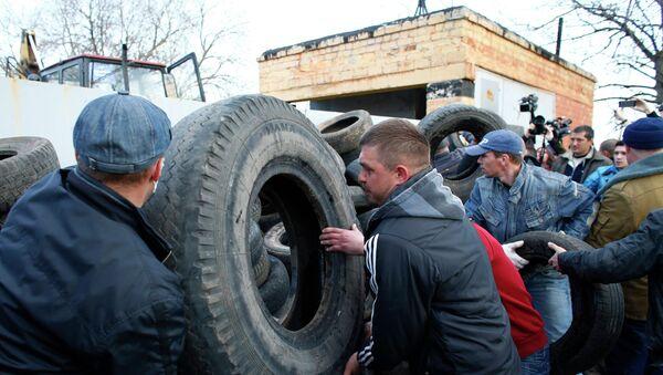 Сторонники федерализации Украины строят баррикаду из покрышек около ворот аэропорта Краматорска