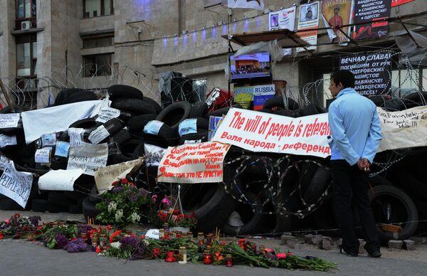 Цветы и свечи в память о погибших в Одессе у окруженного баррикадами здания областной государственной администрации города Донецка