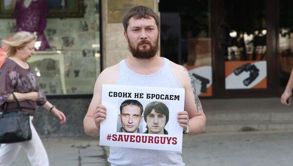 Мужчина держит плакат с фото задержанных на Украине журналистов телеканала Лайф Ньюз Олега Сидякина и Марата Сайченко. Архивное фото