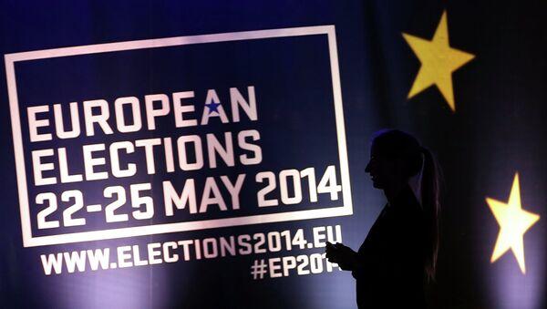 Девушка на фоне баннера с информацией о выборах в Европарламент в Брюсселе. Архивное фото