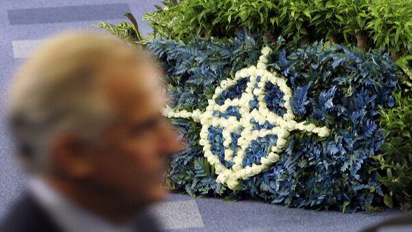 Мужчина проходит мимо логотипа НАТО, выложенного цветами
