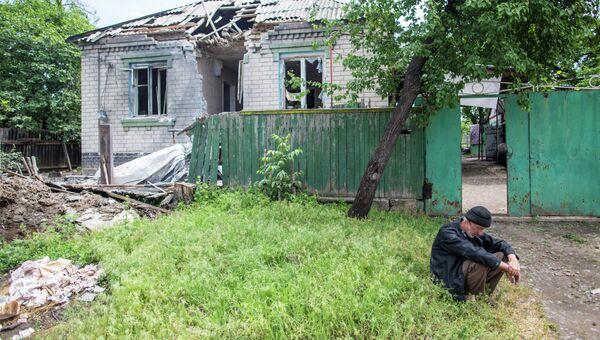Пожилой мужчина возле своего дома, разрушенного в результате попадания снаряда. Архивное фото