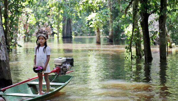 Девочка в лодке на реке Амазонка, возле города Манаус, Бразилия