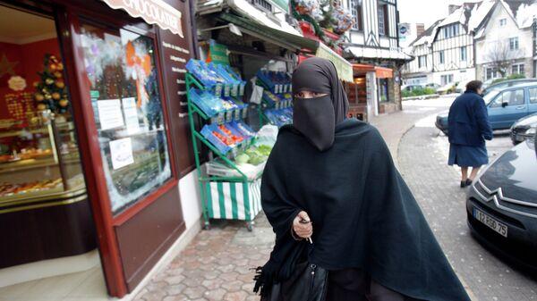 Женщина в никабе на улице Ле-Мениль-Сен-Дени недалеко от Парижа. Архивное фото