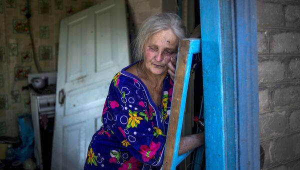 Местная жительница в своем доме, пострадавшем во время авиационного удара вооруженных сил Украины по станице Луганская. 2014 год