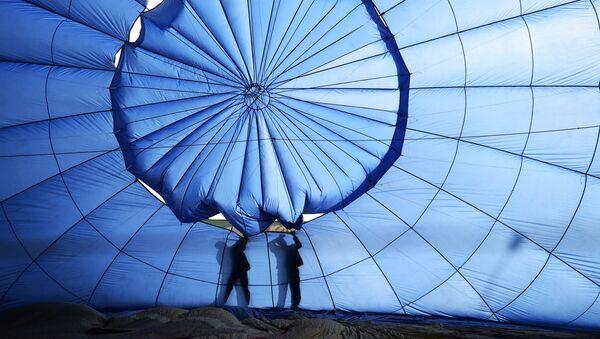 Участники фестиваля подготавливают аэростат к полету перед началом XIII Международного фестиваля воздухоплавания Небесная ярмарка-2014