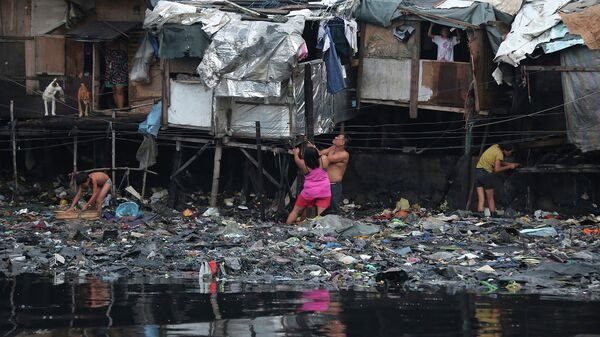 Жители города Манила, Филлипины, у своих жилищ во время тайфуна Раммасун