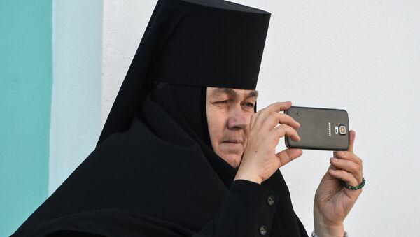 Монахиня фотографирует на мобильный телефон богослужение в Троице-Сергиевой лавре в городе Сергиевом Посаде