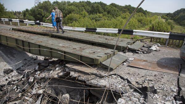 Люди идут мимо разрушенного моста в Донецкой области. Архивное фото