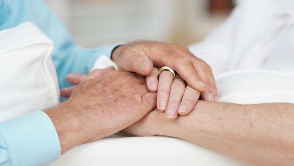 Пожилая пара держатся за руки