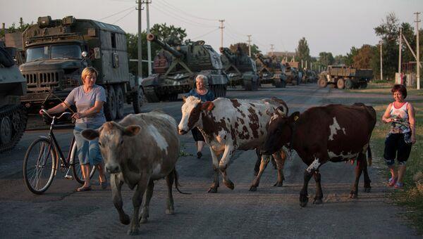 Местные жители на фоне военной техники украинской армии в городе Иловайске. Архивное фото