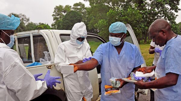 Медицинские работники передают средства индивидуальной защиты от лихорадки Эбола. Архивное фото
