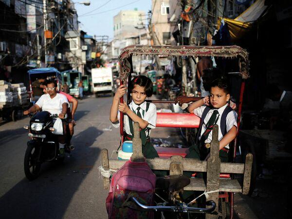 Школьники в одной из рикш в старых кварталах Дели