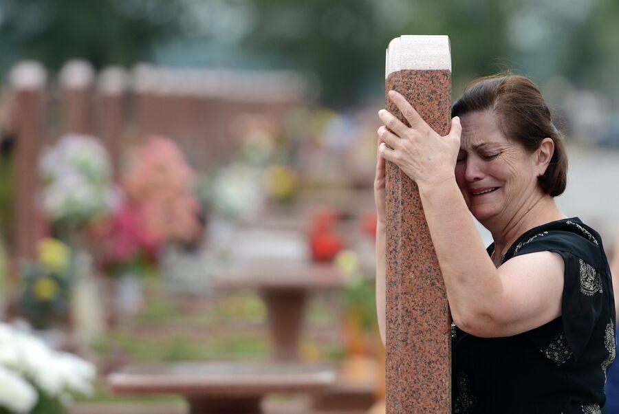 Женщина плачет на мемориальном кладбище Город ангелов в Беслане