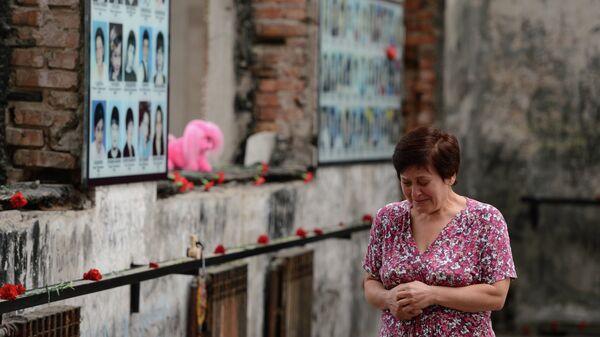 Женщина плачет на траурном мероприятии в годовщину трагедии в Беслане