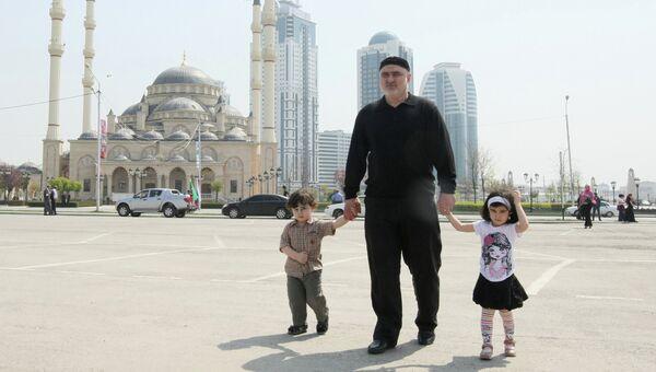 Мужчина с детьми на площади у мечети Сердце Чечни имени Ахмата Кадырова. Архивное фото