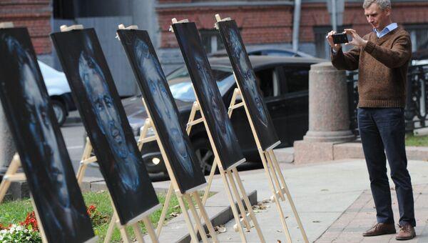 Мужчина фотографирует портреты, нарисованные московскими художниками на акции в память журналистов, погибших в горячих точках
