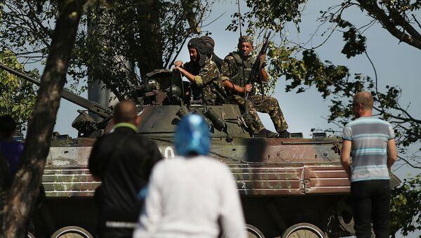 Местные жители наблюдают за украинским танком на окраине стратегического Мариуполя