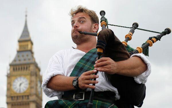 Волынщик и уличный музыкант Дэвид Уитни Абердине играет на волынке в центре Лондона