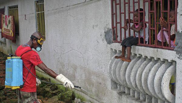 Житель Либерии обрабатывает дом химикатами в попытке предотвратить распространение вируса лихорадки Эбола