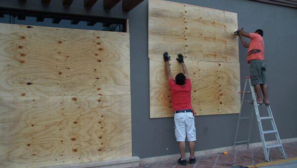 Рабочие укрепляют стену во время приближения урагана Одиль к берегам Мексики
