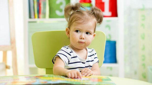Девочка с книгой в детском саду.Архивное фото