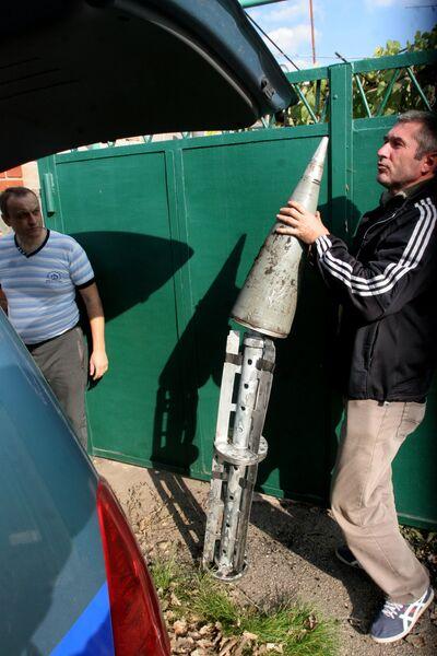 Местные жители рассматривают части ракет, которыми украинские силовики обстреливают Донецк